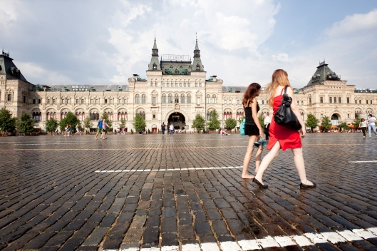 wo girls walk through the Red Square in front of the GUM